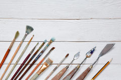 Different brushes to paint on a white wooden background, top vie. W Stock Image