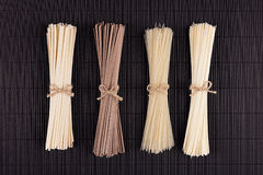 Different bundles raw noodles on black striped mat background with copy space, top view. Different bundles raw noodles  black striped mat background with copy Royalty Free Stock Images