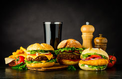 Different Burgers with Cola Fast Food. Fast Food with Cheeseburger, beef burger and Chicken burger and French Fries Royalty Free Stock Image