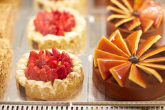 Different cakes in display case in pastry shop Royalty Free Stock Photos