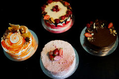 The different cakes smoothly rotate on the base.There is chocolate, carrot, yogurt and berries. Stock Photo