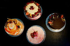 The different cakes smoothly rotate on the base.There is chocolate, carrot, yogurt and berries. Stock Image