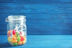 Different candies in glass jar. On wooden background Stock Photos
