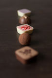 Different candies on a wooden table. Stock Photos