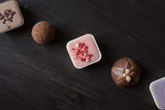 Different candies on a wooden table. Close-up view of different candies on a wooden table viewed from above Stock Images