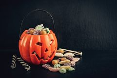 Different candy in bucket. In shape of pumpkin on black background. Halloween concept royalty free stock photo