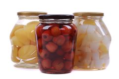 Different canned fruits in glass bottles royalty free stock photos