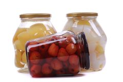 Different canned fruits in glass bottles royalty free stock image