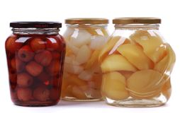 Different canned fruits in glass bottles stock photo