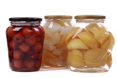Different canned fruits in glass bottles stock images