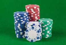Different casino chips on a green table Stock Photo