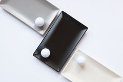 Different ceramic dishes with golf balls on over white backgroun Stock Images