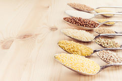 Different cereals grain in spoons on beige wood board, rustic background. Stock Photos
