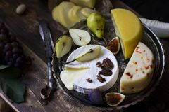 The different cheese, fresh fruits and garden flowers. On wooden table royalty free stock image