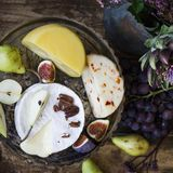 The different cheese, fresh fruits and garden flowers. On wooden table stock photo