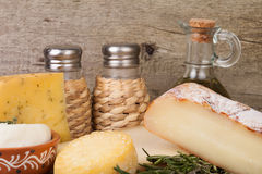 Different cheese, olive oil, rosemary, salt and pepper on a wood Stock Photo
