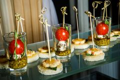 Different cheese snack arranged on glass surface. Cheese snack with tomatoes, basil and bread arranged on glass surface on catering service banquet stock photos