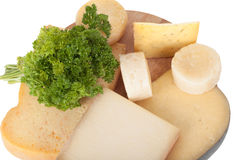Different cheeses and a bunch of parsley lying on a board isolat Stock Photos
