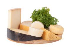 Different cheeses and a bunch of parsley lying on a board isolat Royalty Free Stock Photos