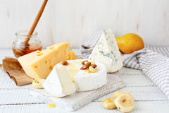 Different cheeses on a cutting board Stock Photos