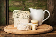 Different cheeses and milk in a jug Stock Photos