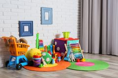 Different child toys on floor. Against brick wall royalty free stock image