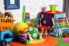 Different child toys on floor. Against brick wall stock image