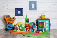 Different child toys on floor. Against brick wall stock images