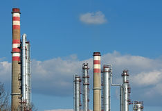 Different chimneys  of oil refinery and blue sky Stock Photos