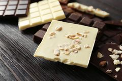 Different chocolate bars with nuts. On wooden background Stock Photos