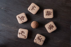 Different chocolate candies on a wooden table. Different candies on a wooden table viewed from above Royalty Free Stock Image