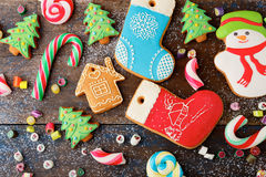 Different Christmas Gingerbread cookies and mixed candy. On wooden background Royalty Free Stock Photos