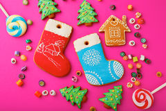 Different Christmas Gingerbread cookies and mixed multicolored candy. On pink background Royalty Free Stock Photos