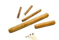 Different cigars and cigarillos with matches. On white Stock Photo