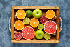 Different citrus fruit on a wooden box and grey concrete table. Food background. Healthy eating. Antioxidant, detox. Dieting, clean eating, vegan, fitness or royalty free stock images
