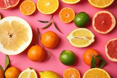 Different citrus fruits on color background. Top view royalty free stock photo
