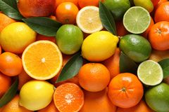 Different citrus fruits with leaves as background. Top view royalty free stock photos