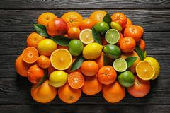 Different citrus fruits with leaves on black background stock photography