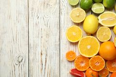 Different citrus fruits on wooden background. Top view. Space for text stock images