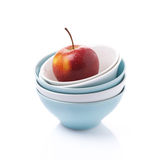 Different clean bowl and red apple, isolated Stock Photo