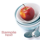 Different clean bowl, spoons and red apple, isolated Royalty Free Stock Image