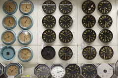 Different clocks with information and price tags on the wall for sale stock images