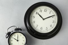 Different clocks on light background. Time change royalty free stock image