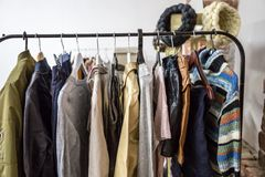 Different clothes and bags on the shelves and hangers Royalty Free Stock Photos