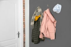 Different clothes hanging on grey wall near door. Hallway interior elements stock photos