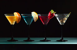 Different cocktails garnished with fruits. On black background royalty free stock photos