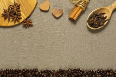 Different coffee ingredients on brown textile cloth. Ingredients for tasty coffee - roasted beans and different spices such as cinnamon, anise and clove on the royalty free stock image