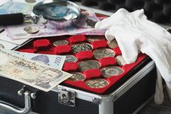 Different coins and banknotes with a magnifying glass stock photography