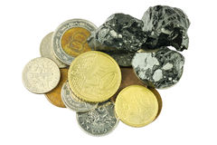 Different coins and raw coal on top Stock Image
