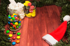 Different color candies on wooden background with tinsel. Copy space. Different color candies on red wooden background with green tinsel like frame and Santa Stock Photos